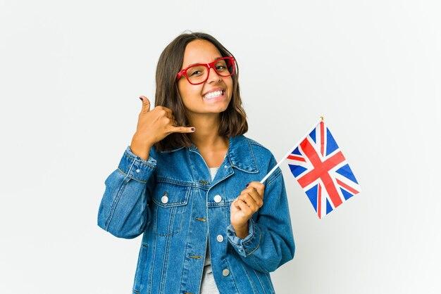 Jonge vrouw die een engelse vlag houdt die op witte muur wordt geïsoleerd die een mobiel telefoongesprekgebaar met vingers toont