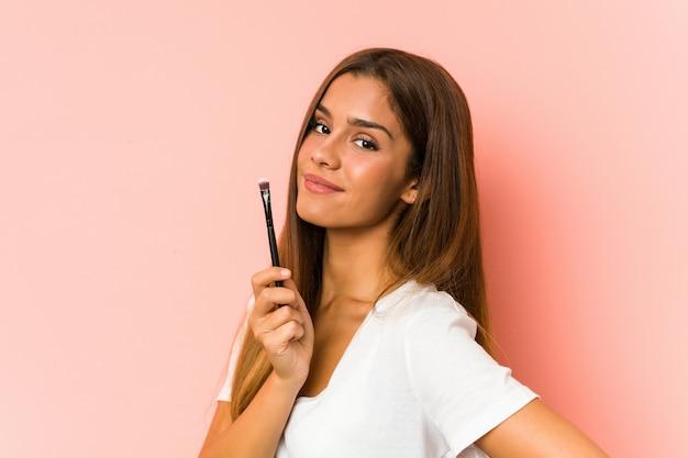 Jonge vrouw die een eyebrush houdt