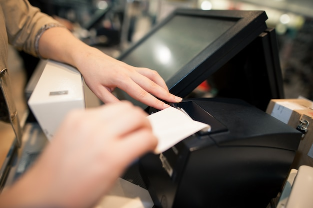 Jonge vrouw die een factuur / bon voor een klant afdrukt in een enorm winkelcentrum