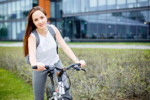 Jonge vrouw die een fiets in de stad berijdt.