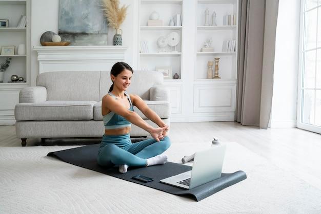 Jonge vrouw die een fitnessmat gebruikt om te trainen