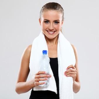Jonge vrouw die een fles water houdt