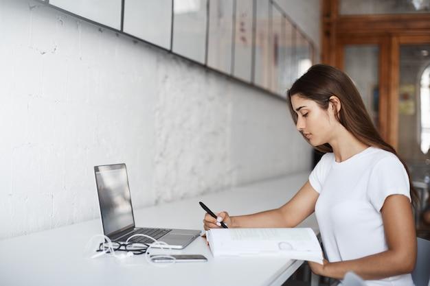 Jonge vrouw die een foreing taal leert die een laptop computer en een boek gebruikt. zittend in een lichte coworking-ruimte. onderwijs concept.