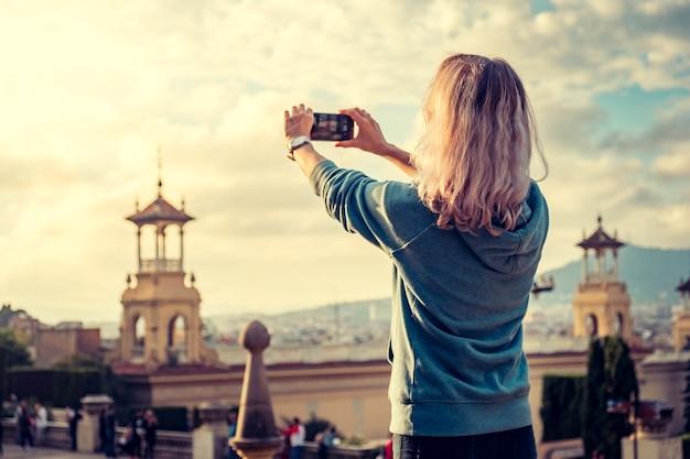 Jonge vrouw die een foto maakt van een stad