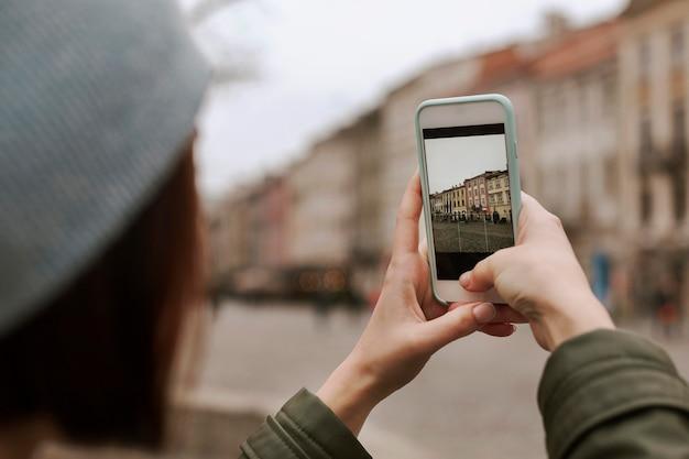 Jonge vrouw die een foto met haar telefoon neemt