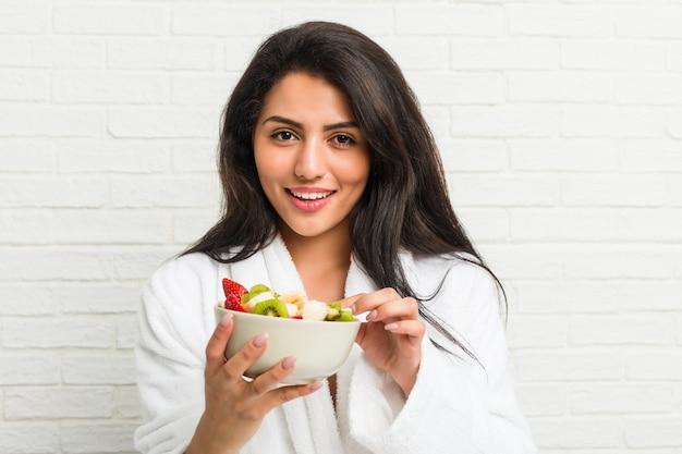 Jonge vrouw die een fruitkom op het bed eet