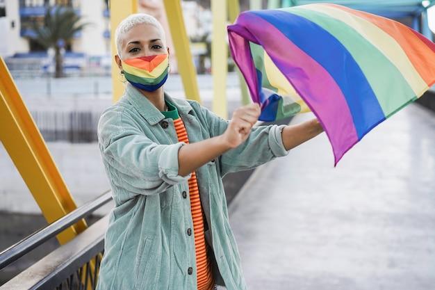 Jonge vrouw die een gay pride-masker draagt terwijl ze de lgbt-vlag zwaait - focus on face