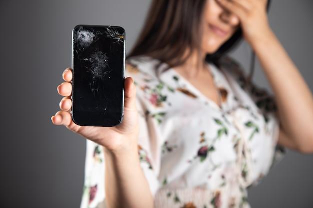 Jonge vrouw die een gebroken telefoon toont die haar gezicht bedekt