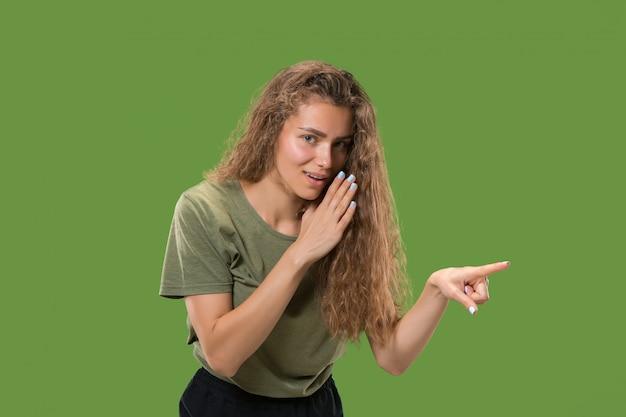 Jonge vrouw die een geheim achter haar hand fluistert