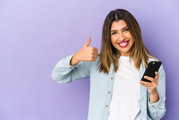 Jonge vrouw die een geïsoleerde telefoon houdt die en duim opheft
