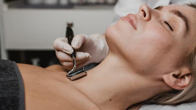 Jonge vrouw die een gezichtsbehandeling en halsbehandeling krijgt