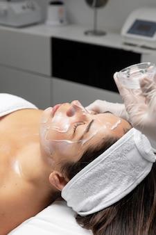 Jonge vrouw die een gezichtshuidverzorgingsbehandeling heeft