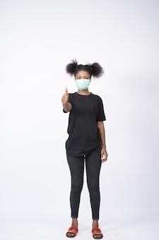 Jonge vrouw die een gezichtsmasker draagt, dat duimen opgeeft