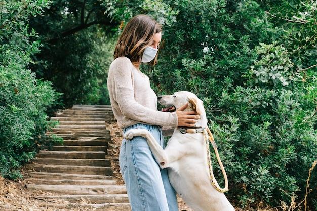 Jonge vrouw die een gezichtsmasker draagt dat een hond streelt die in het park speelt. concept van nieuw normaal buitenshuis.