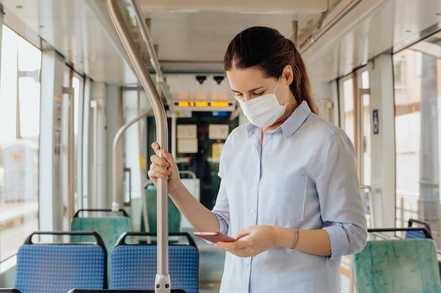 Jonge vrouw die een gezichtsmasker draagt en aan de telefoon praat tijdens het reizen met het openbaar vervoer