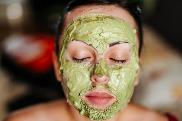 Jonge vrouw die een gezichtsmasker draagt. huidverzorging concept