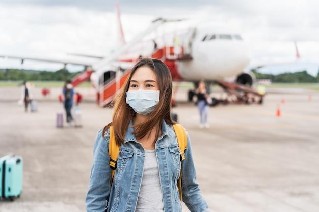 Jonge vrouw die een gezichtsmasker draagt op de luchthaven