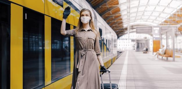 Jonge vrouw die een gezichtsmasker en handschoenen draagt en in een treinstation zwaait - covid-19