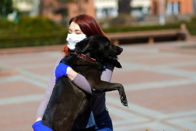 Jonge vrouw die een gezichtsmasker gebruikt als een coronavirus-preventie die met haar hond loopt. wereldwijd covid-19 pandemisch conceptbeeld.