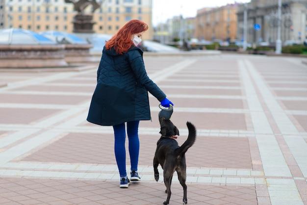 Jonge vrouw die een gezichtsmasker gebruikt als een coronavirus-preventie die met haar hond loopt