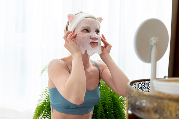 Jonge vrouw die een gezichtsmasker voor zelfzorg gebruikt