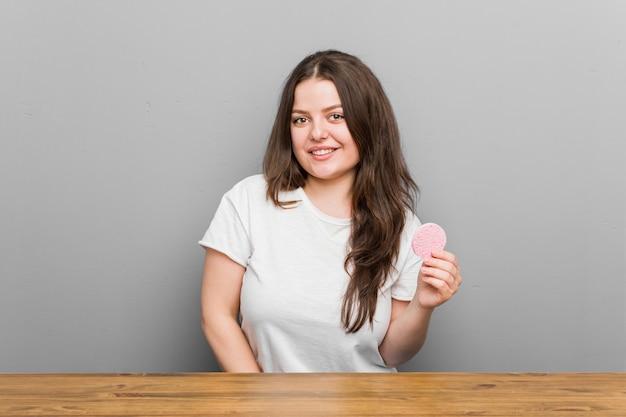 Jonge vrouw die een gezichtsspons gelukkig, glimlachend en vrolijk houdt.