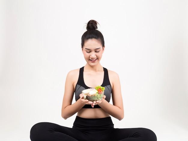 Jonge vrouw die een gezonde fruitsalade na training eet.