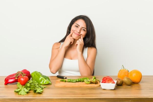 Jonge vrouw die een gezonde maaltijd voorbereidt die tussen twee opties twijfelt.