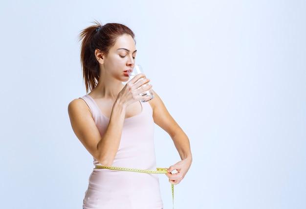 Jonge vrouw die een glas water drinkt terwijl ze haar tailleomvang meet