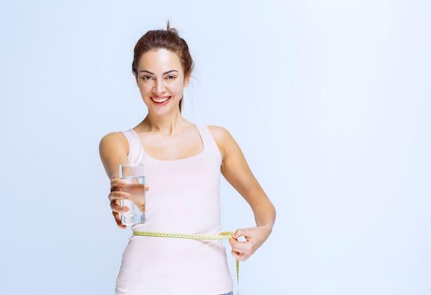 Jonge vrouw die een glas zuiver water vasthoudt en haar tailleomvang meet