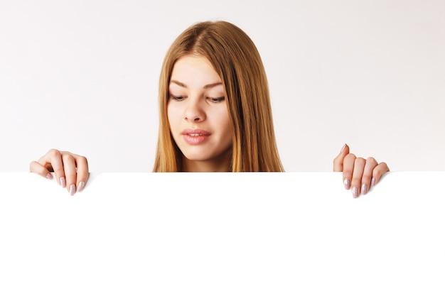 Jonge vrouw die een groot billboard vasthoudt en erop neerkijkt.