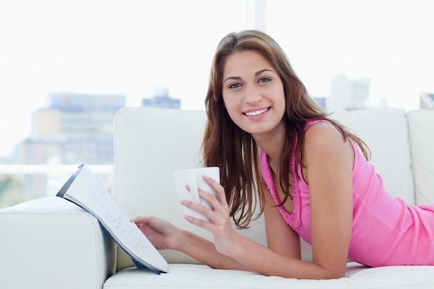 Jonge vrouw die een grote glimlach toont terwijl het lezen van en het drinken van koffie
