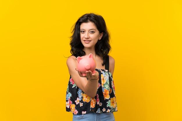 Jonge vrouw die een grote spaarpot houdt