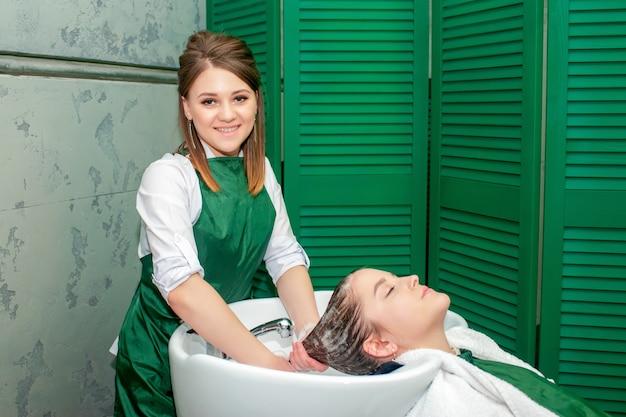 Jonge vrouw die een haarwas in schoonheidssalon krijgt.