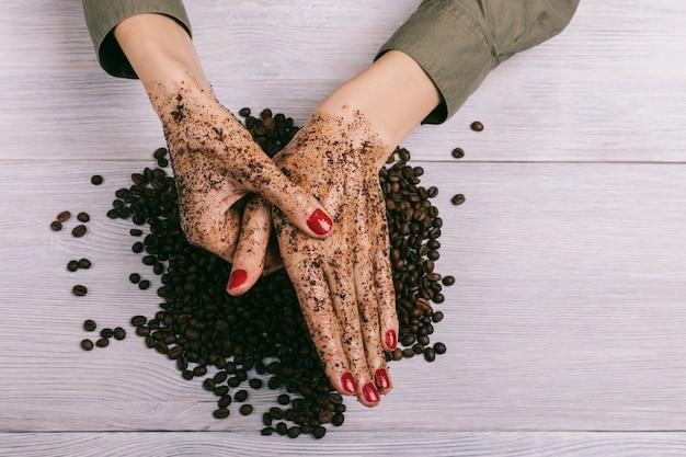 Jonge vrouw die een hand met koffiescrub masseert