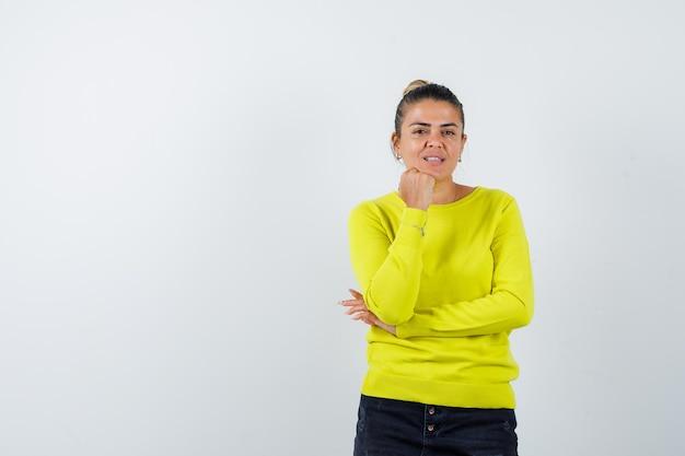 Jonge vrouw die één hand onder de kin houdt en een andere hand op de elleboog houdt in gele trui en zwarte broek en peinzend kijkt looking