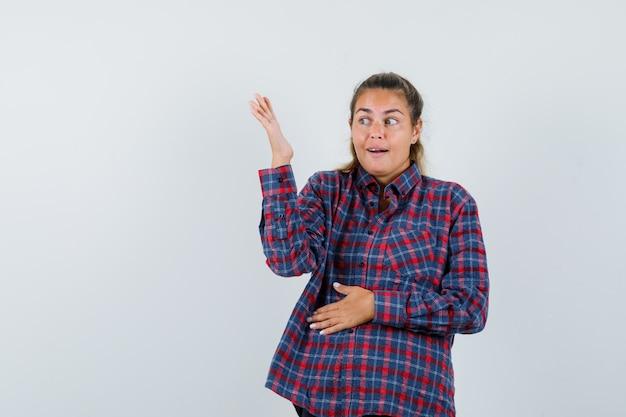 Jonge vrouw die een hand op de buik rust terwijl ze een andere hand uitrekt en ernaar kijkt in een geruit overhemd en er mooi uitziet