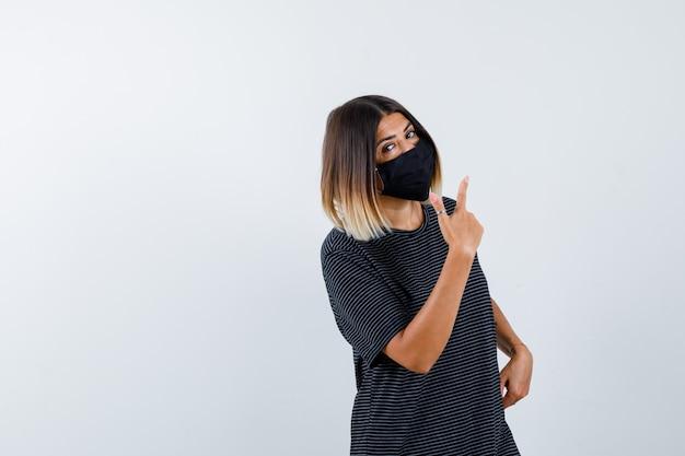 Jonge vrouw die een hand op de taille houdt, omhoog wijst in zwarte jurk, zwart masker en serieus kijkt, vooraanzicht.