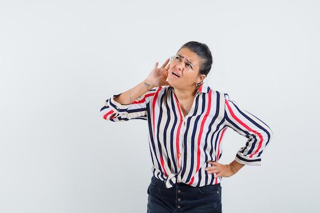 Jonge vrouw die één hand op taille legt, een andere hand dichtbij oor en iets in gestreepte blouse probeert te horen en gefocust kijkt.