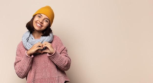 Jonge vrouw die een hartsymbool met haar gelukkige handen doet voelen