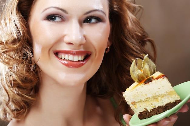 Jonge vrouw die een heerlijk stuk van een cake steunt