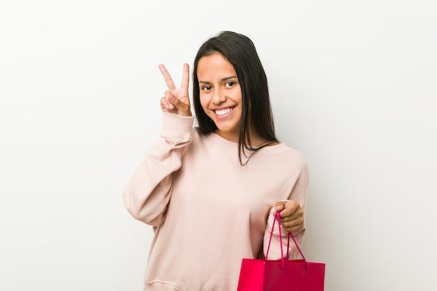 Jonge vrouw die een het winkelen zak houdt die overwinningsteken toont en breed glimlacht.