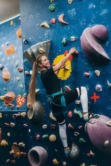 Jonge vrouw die een hoge, indoor, kunstmatige klimmuur beklimt