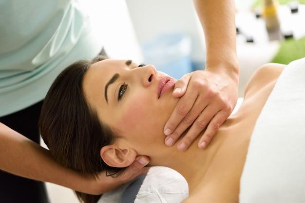 Jonge vrouw die een hoofdmassage in een kuuroordcentrum ontvangt.