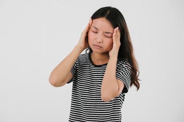 Jonge vrouw die een hoofdpijn heeft
