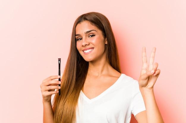 Jonge vrouw die een huidborstel houdt die nummer twee met vingers toont