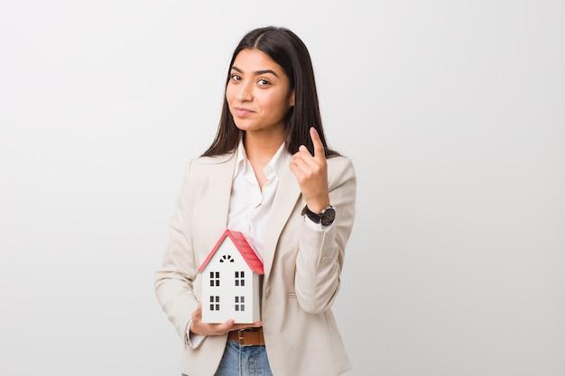 Jonge vrouw die een huispictogram houdt die met vinger op u richten alsof uitnodigend dichter komt