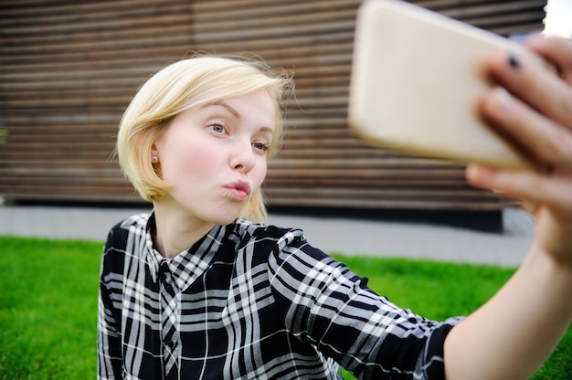 Jonge vrouw die een in openlucht zelfportret (selfie) met slimme telefoon neemt