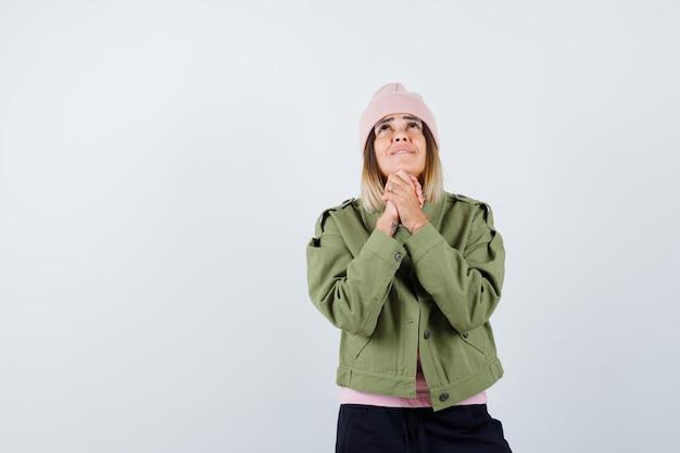Jonge vrouw die een jas aan het bidden is