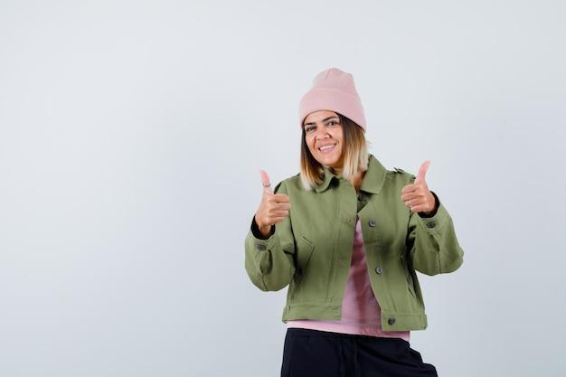 Jonge vrouw die een jasje draagt dat duimen laat zien